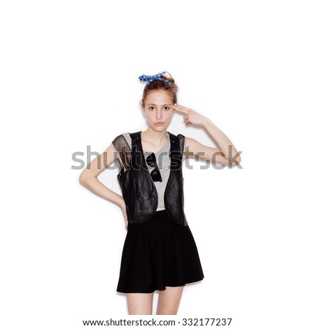 Fashion swag young woman wearing black leather jacket and skirt and showing shoot of gun . Girl having fun. White background, not isolated - stock photo