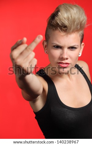 Fashion teenager girl showing middle finger isolated on a white background - stock photo