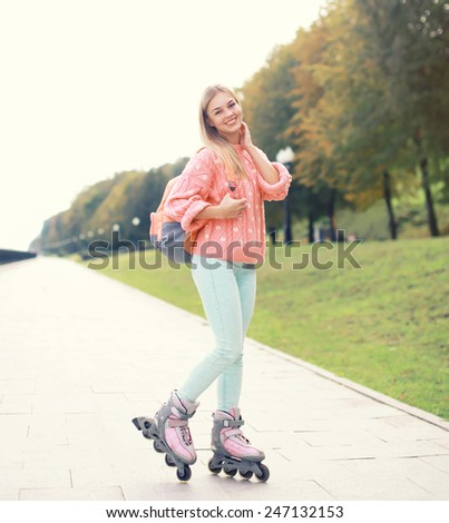 Fashion, vacation and people concept - pretty stylish smiling roller girl in the city park - stock photo