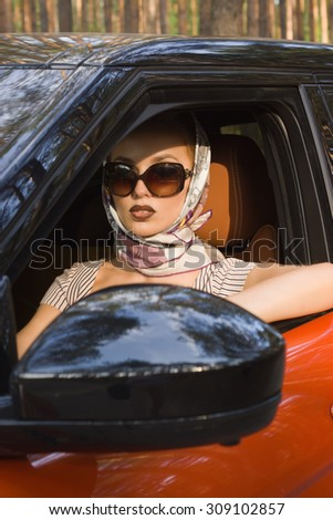 Fashion vintage woman behind steering wheel - stock photo