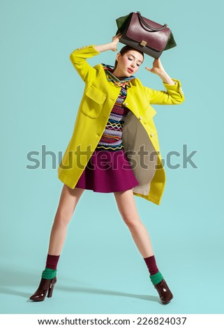 Fashion vogue model pose on light background bag on head - stock photo