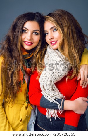 Fashion winter portrait of blonde and brunette beautiful best friends girls, hugs and having fun. Wearing bright stylish cashmere sweaters and scarfs. Have trendy make up and long amazing hairs. - stock photo