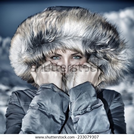 Fashion wintertime look, vintage style photo of gorgeous female wearing warm stylish coat with furry hood, fashionable winter clothes, vogue concept  - stock photo