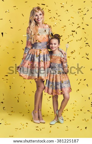 Fashion woman and a pretty little girl wearing the same dresses. Photo of mother and daughter, golden confetti - stock photo