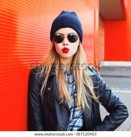 Fashion woman blowing lips with red lipstick wearing a rock black style having fun in city - stock photo