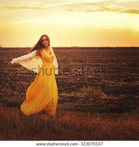 Fashion woman dressed in long yellow dress and white jersey dancing on a sunset autumn field. - stock photo