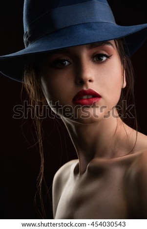 Fashion woman gangster style with handgun pistol on black background - stock photo
