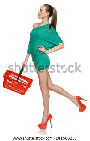 Fashion woman in full length wearing green dress and high heels red shoes walking with empty shopping basket. Isolated on white background - stock photo