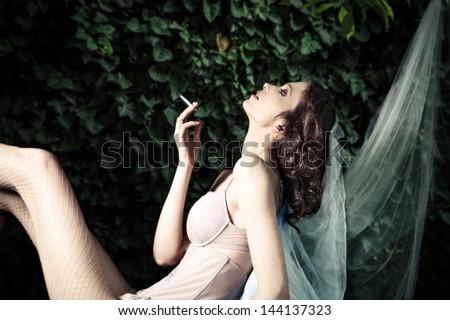fashion  woman in garden smoking,  side view - stock photo