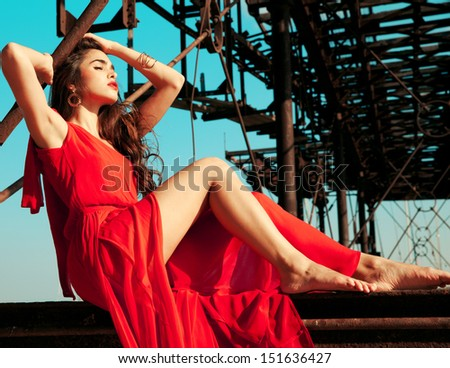 fashion woman in red dress on a old bridge. Horizontal shot, outside - stock photo