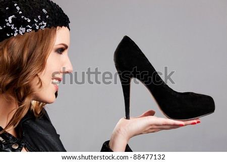 Fashion woman looking at high-heel shoes and smiling - stock photo