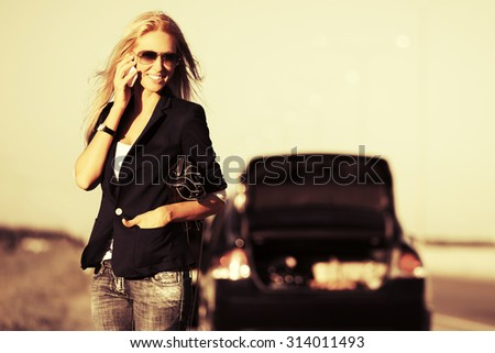 Fashion woman next to broken car calling on cell phone  - stock photo