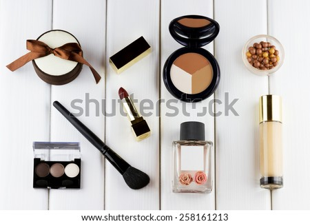 Fashion woman objects. Makeup and cosmetic set: lipstick, foundation, concealer, eyeshadow palette, blusher balls, perfume on white wooden background - stock photo
