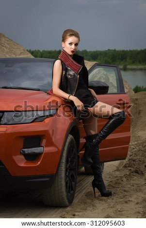 Fashion  woman standing near vehicle with opened door - stock photo