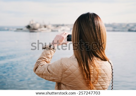 Fashion  woman taking photo with cellphone on the coast on spring. Happy girl on vacation taking picture on sea background. - stock photo
