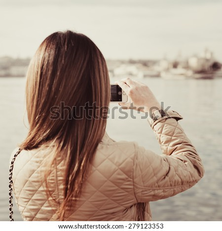 Fashion  woman taking photo with cellphone on the coast on spring. Happy girl on vacation taking picture on sea background. Photo with instagram style filters - stock photo