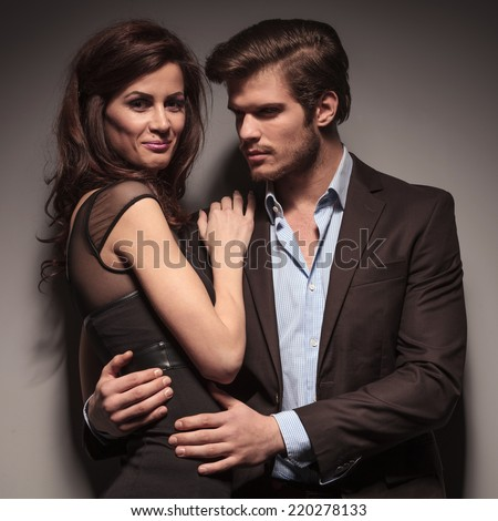 Fashion woman wearing a elegant black dress smiling into the camera while the boyfriend is embracing her looking away from the camera. - stock photo