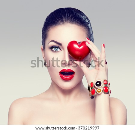 Fashion woman with red heart. Valentine's day art portrait. Beautiful make up and manicure. Surprised model girl face, open mouth, emotion - stock photo