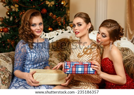 fashion women exchanging gifts in front of Christmas tree - stock photo