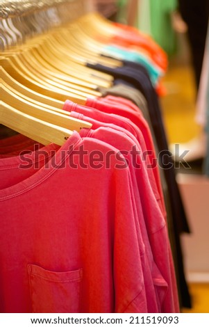 fashion women's t-shirts hanging in trendy boutique - stock photo