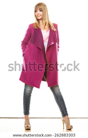 Fashion. Young blonde fashionable woman in vivid color pink coat. Female model posing isolated on white background - stock photo