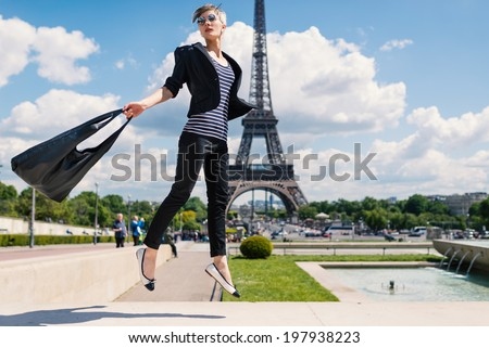 Fashion young blonde woman jumping portrait in front of the Eiffel Tower in Paris, France.  - stock photo