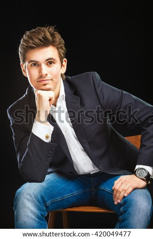 Fashion young businessman black suit on dark  background - stock photo