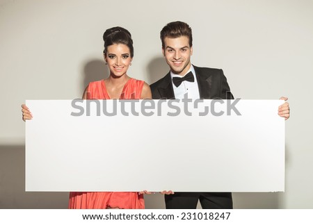 Fashion young elegant couple smiling while holding a white board. - stock photo