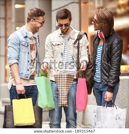 Fashion young guys go shopping with many colored shopping bags in their hands, watch purchase. In the background window dressing. - stock photo