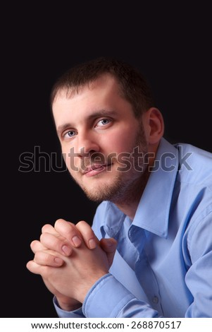 Fashion young man in a blue shirt, portrait on black background - stock photo