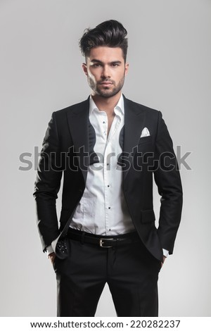 Fashion young man in tuxedo looking at the camera while holding his hands in pocket. On grey background. - stock photo