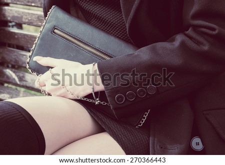 Fashion young woman holding black purse clutch in hand closeup. Instagram style look. - stock photo