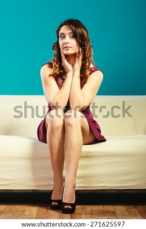 Fashion young woman in full length. Girl in fashionable dress high heels sitting on couch vivid color blue background - stock photo