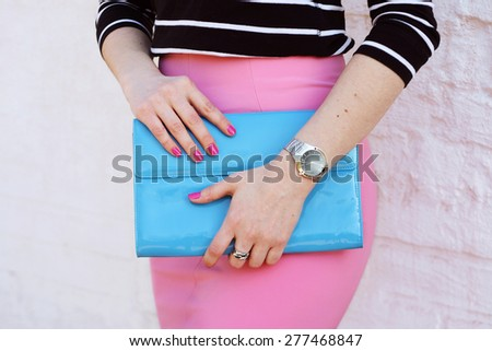 Fashion young woman in pink skirt and black blouse with stylish blue clutch , accessories, watch white background - stock photo