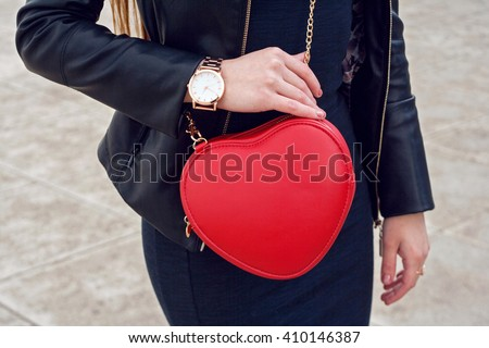 Fashion young woman with red handbag street background. Trendy accessories gold watch , stylish outfit leather jacket and dress - stock photo
