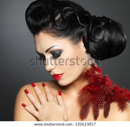 Fashion young woman with red nails, creative hairstyle and makeup - Model posing in studio - stock photo