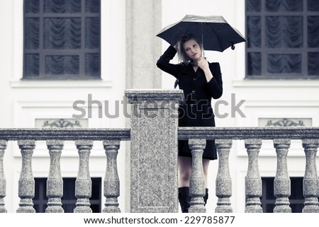 Fashion young woman with umbrella in the rain - stock photo