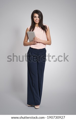 Fashionable and smiling business woman with digital tablet - stock photo