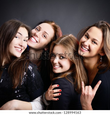 fashionable attractive happy party teen girls smiling over black background - stock photo