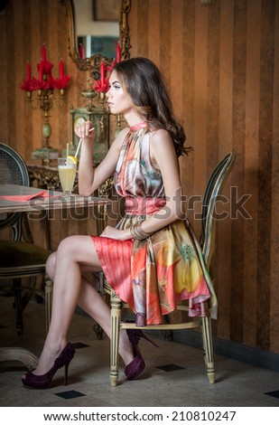 Fashionable attractive woman in multicolored dress sitting in restaurant. Beautiful brunette posing in elegant vintage scenery with a juice glass. Attractive female drinking lemonade in cafeteria - stock photo