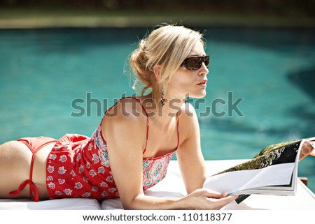 Fashionable attractive woman lounging by a swimming pool, reading a magazine and wearing shades. - stock photo