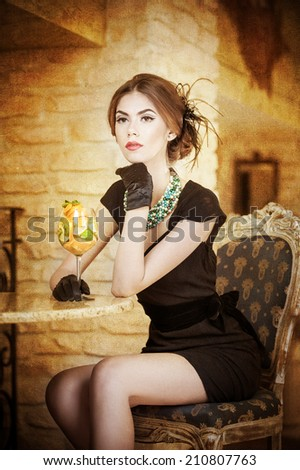 Fashionable attractive young woman in black dress sitting in restaurant. Beautiful brunette posing in elegant vintage scenery with a juice glass. Attractive lady with gloves in luxurious interior - stock photo