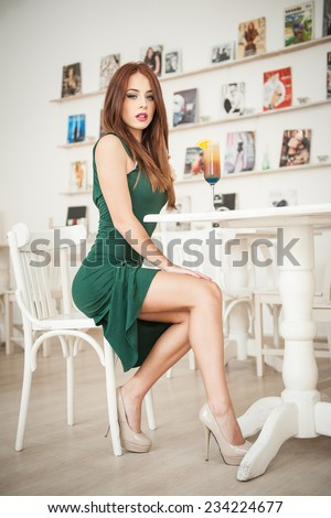 Fashionable attractive young woman in green dress sitting in restaurant. Beautiful redhead posing in elegant scenery with an orange juice glass on the table. Pretty female relaxing, indoor shot. - stock photo