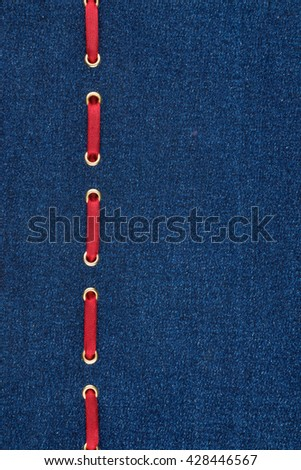 Fashionable background red satin ribbon inserted in denim, with space for your creativity - stock photo