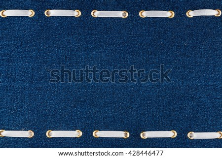 Fashionable background white satin ribbon inserted in denim, with space for your creativity - stock photo