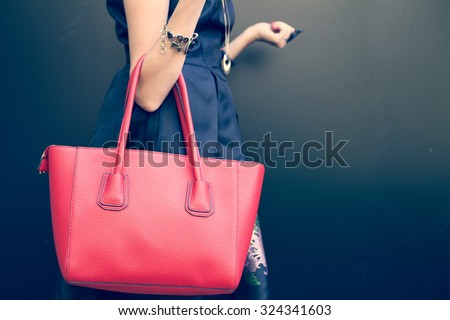 Fashionable beautiful big red handbag on the arm of the girl in a fashionable black dress, posing near the wall on a warm summer night. Warm color - stock photo
