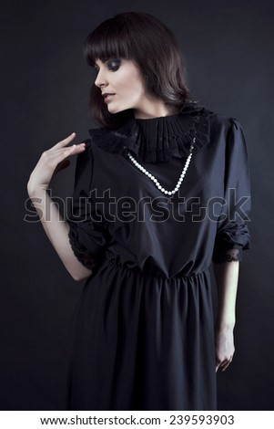 Fashionable beautiful blonde woman with dark lips in black on the studio. Gothic. - stock photo