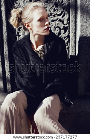 Fashionable beautiful blonde woman with red lips in a black coat on the street. Gothic. - stock photo