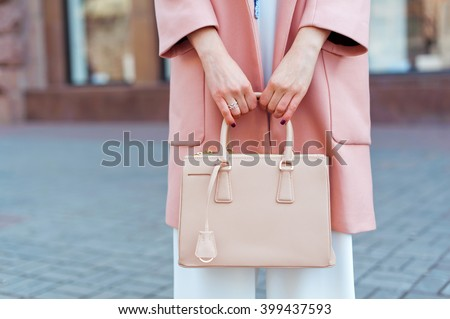 Fashionable beautiful woman with handbag in pink coat, white overalls and blue shoes on the city streets. - stock photo