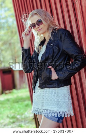Fashionable beautiful young blond wearing a leather jacket and leans against the red wall - stock photo